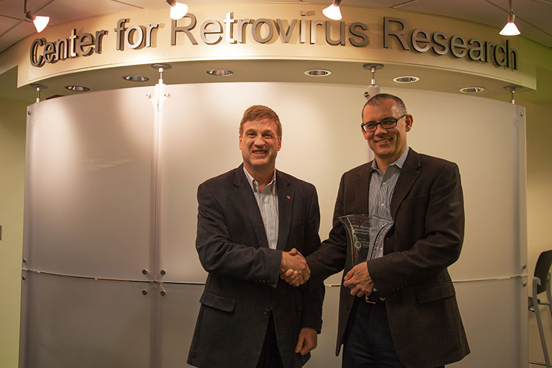 Dr. Paul Bieniasz (right) receives Career Award crystal from Center for Retrovirus Research Director Dr. Patrick L. Green (left).